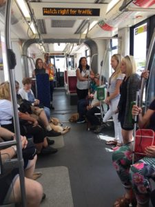 group listening to presenter while seated or standing in the stationary streetcar