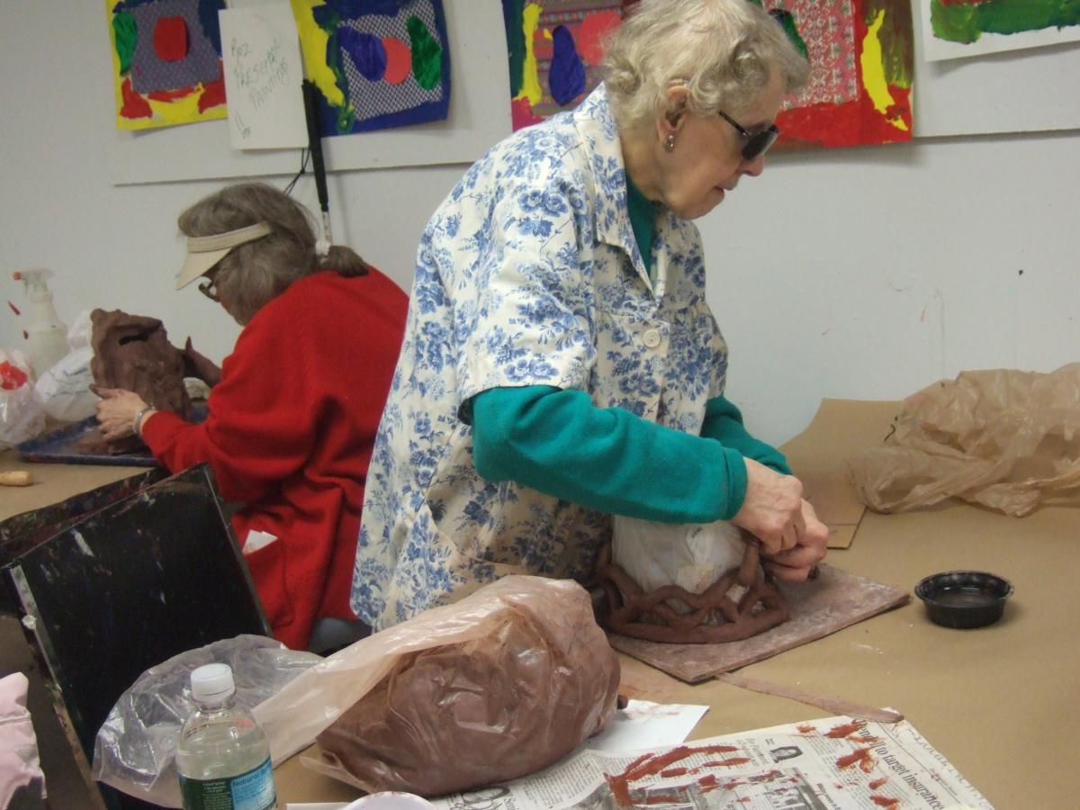 Senior citizen (woman) is working with block of clay in a group setting.