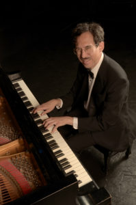 Michael A. seated at a grand piano, hands on the keys, dressed in a black suit, white shirt, and bow tie. He is smiling up at the camera.